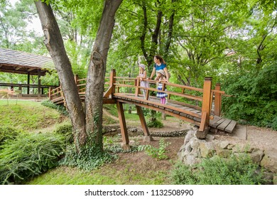 Mother and Little girls in elegant dress and hat on wooden bridge in nature, family spring day outdoor