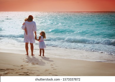 Mother with little girls looking at sunset on tropical beach
