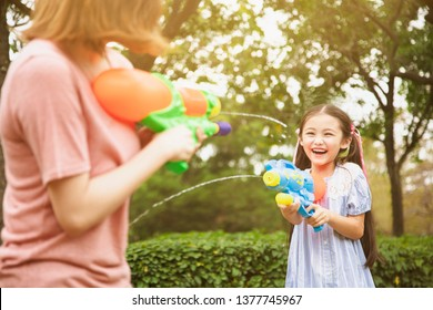 mother and little girls playing water guns in the park