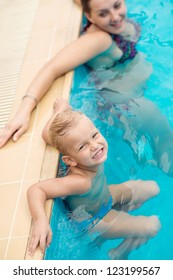 Mother and little kid relaxing in a swimming pool