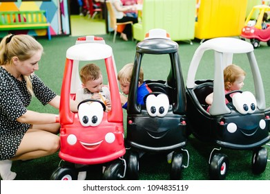 Mother and little kids the boys, girls child rides on a red, black big car on the road. Close up. The baby is driving the car and played in a children's playroom on a birthday party.