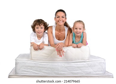 Mother and little kids sitting on a lot of mattresses, isolated on white background