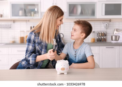 Mother with little son breaking piggy bank with hammer at home