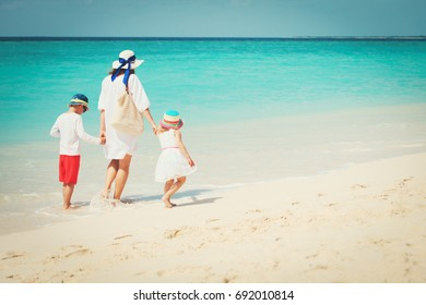 mother with little son and daughter walk on beach