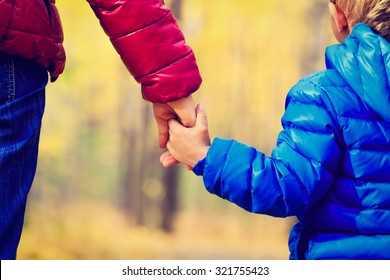 mother and little son holding hands in autumn park