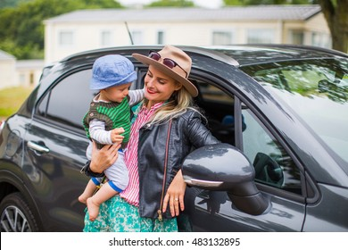 mother and little son near the car, she holds him in her arms