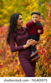 Mother with little son wearing hat, scarf and sweater stands and smiles in park on background of colorful autumn fallen leaves.