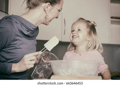 Mother and little toddler daughter having fun whilst baking in the kitchen.