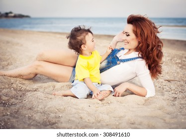 Mother with long curly red hair playing with her son on the beach. Happy family enjoying relaxing and enjoying life in nature. Outdoor shot. Copyspace