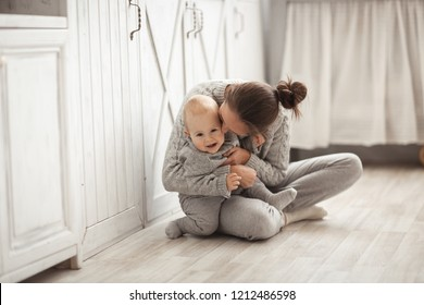 mother with long hair and baby boy hug and kiss, real Scandinavian style interior. The concept of motherhood and safety.