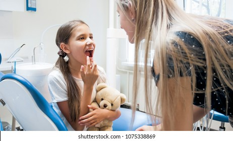 Mother looking at her daughters teeth after teeth treatening in dentist office