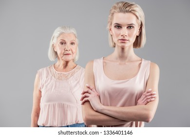 Mother looking out. Emotionless young girl with blonde hair categorically standing while her mother staying behind