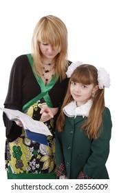 Mother is looking at school record book. Pupil is standing with woman. Isolated on white in studio.