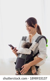 Mother looking at a smartphone while holding a baby