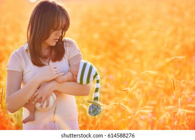 Mother looks at the newborn with tenderness, skillfully holds it in her arms. She stands in the rays of the setting sun on a yellow wheat field