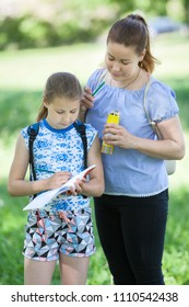 Mother looks in sketchbook, holding color pencils and help daughter to draw at nature