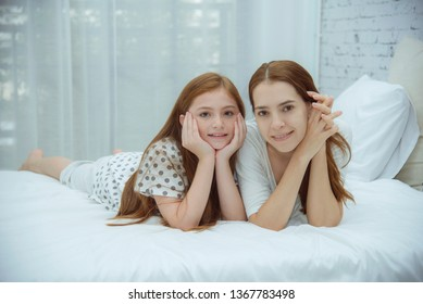 Mother love daughter laying together on bed , little girl happiness with mum in the bedroom, good healthy when parent each other with daughter at home