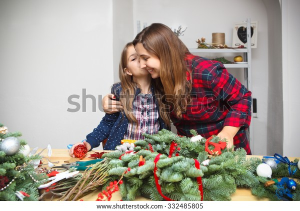 Mother making an advent wreath with daughter - dressed for the christmas