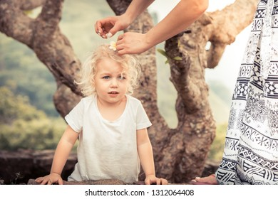 Mother making haircut with flower for kid girl during travel holidays concept care parenting