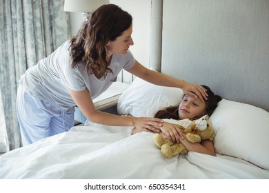 Mother making her daughter sleep in bedroom at home