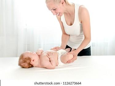 Mother massaging her infant baby