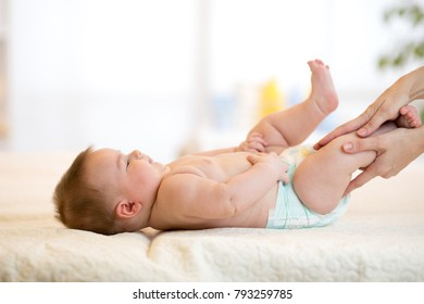 Mother or masseuer massaging baby infant in nursery room
