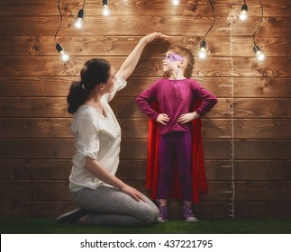 Mother measures the growth of her child daughter at a wooden wall.