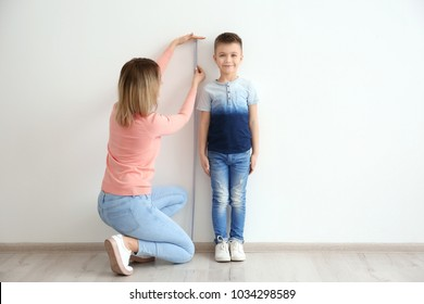 Mother measuring height of little boy near light wall