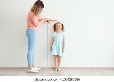 Mother measuring height of little girl near light wall