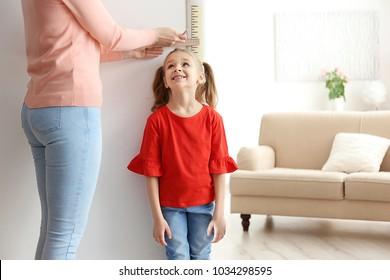 Mother measuring height of little girl near door