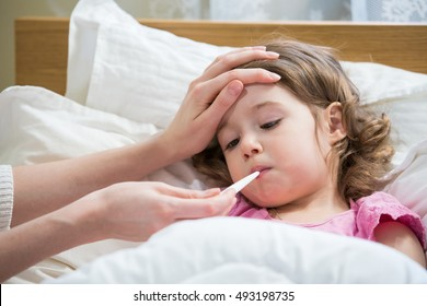 Mother measuring temperature of her ill kid. Sick child with high fever laying in bed and mother holding thermometer. Hand on forehead.