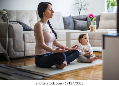 mother meditates with her daughter in the living room