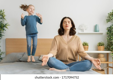 Mother is meditating and her kid is jumping on the bed. Family holiday and togetherness.