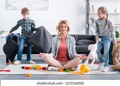mother meditating in lotus position and smiling at camera while kids playing at home