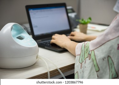 Mother or mom worker pumping breastmilk by Automatic breast pump machine wirh Nursing fabric cover while typing on laptop pc computer on table. Motherhood in corporate office.