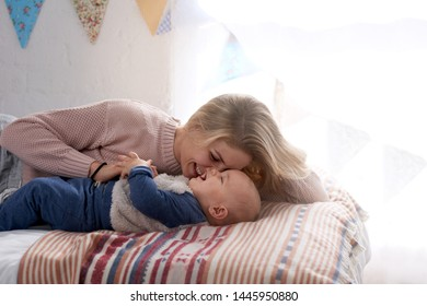 Mother mum mom and child lying on bed together, smiling laughing playing tickles in nursery motherhood childhood
