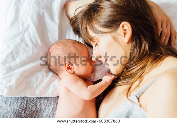 Mother with newborn baby on the bed at home. Beautiful conceptual image of Maternity.