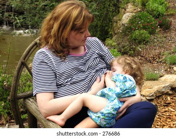 mother nursing baby in outdoor setting