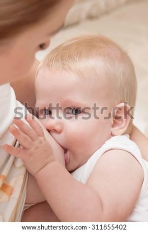 d955759510a66 Mother in nursing bra and t-shirt nursing ( breastfeeding ) her baby,  sitting