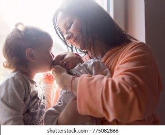 : Mother and older daughter enjoy a new family member kissing him on the first morning sunshine