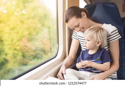 Mother and one year old son riding a train- parenting childhood concepts