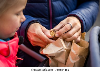 mother opening a roasted chestnut from a sale on a market, child looking on