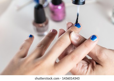 A mother paints her young girl's hands with blue and pink nailpolish, viewed against an isolated white background