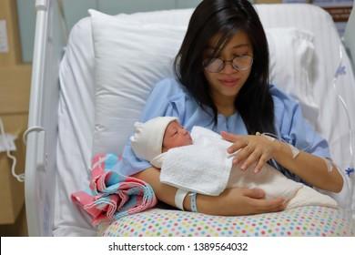 mother parenting, mom using hand help a baby newborn belch burping after breastfeeding milk