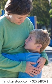 A mother parents her son at a playground