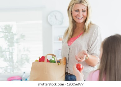 Mother passing tomato to child from paper grocery bag in ktichen