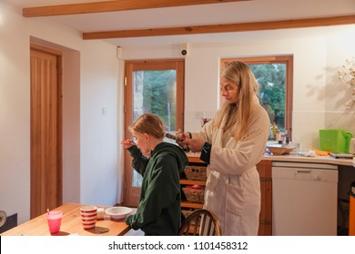 Mother plaiting her daughters hair as she eats her breakfast in the kitchen.