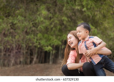Mother play enjoying with her son in outdoor.