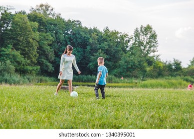 mother play with son in ball at green field. outdoors summer time