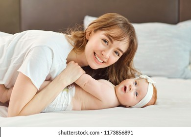 Mother playing with baby on the bed.